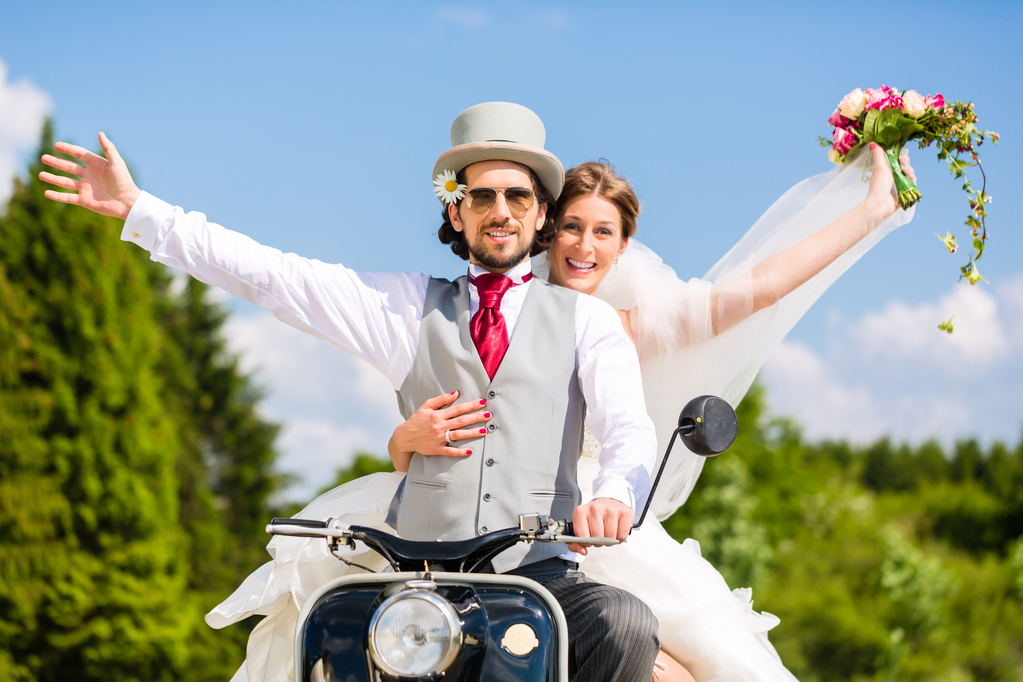 Bridal pair driving motor scooter wearing gown and suit