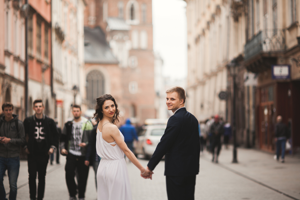 Gorgeous wedding couple, bride, groom kissing and hugging standing in the crowd