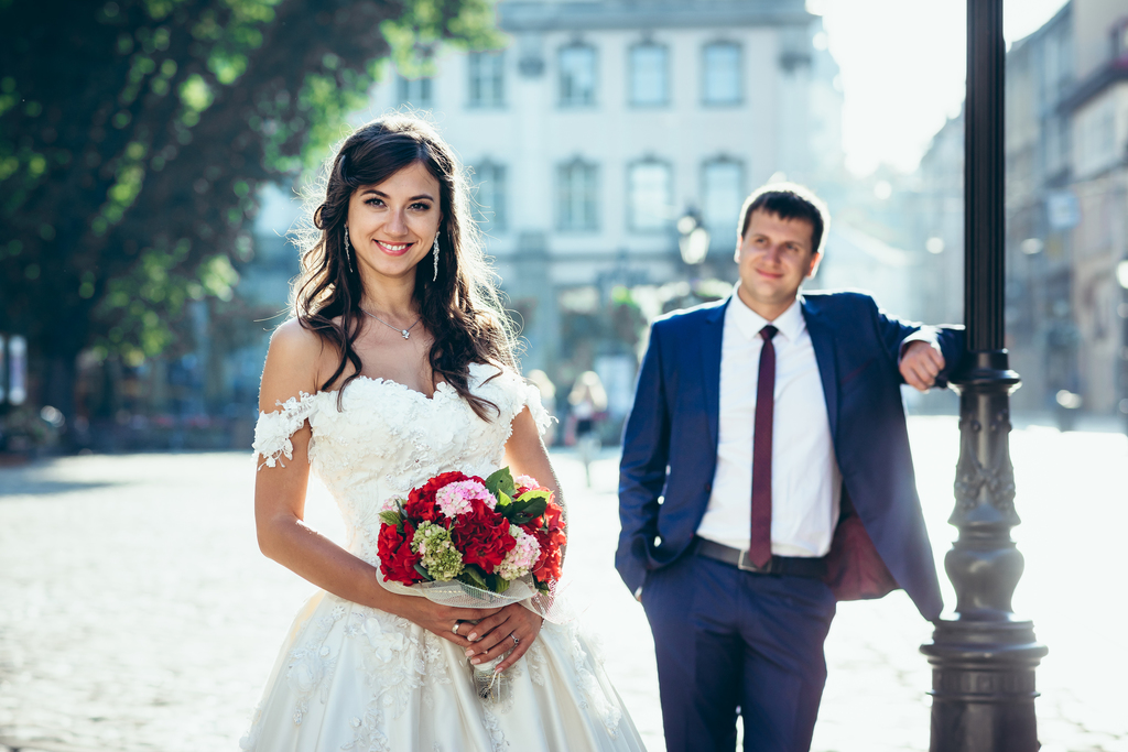 Smiling bride with the red and pink wedding bouquet of flowers at the blurred background of the groom leaning on the street lamp.