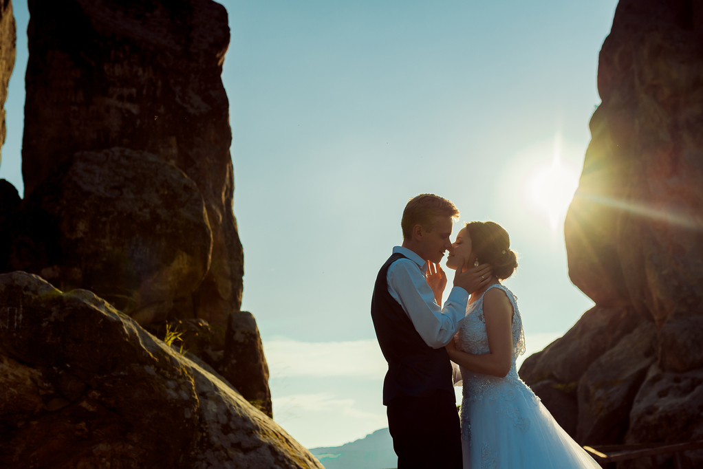 Romantic outdoor portrait of the beautiful young newlywed couple going to kiss during the sunset.